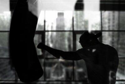 Papiers peints Boxer frappe un sac de boxe contre la fenêtre, séance d'entraînement