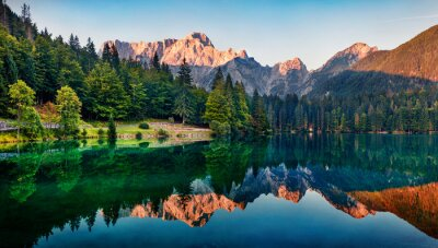 Papiers peints Calm morning view of Fusine lake. Colorful summer sunrise in Julian Alps with Mangart peak on background, Province of Udine, Italy, Europe. Beauty of nature concept background.