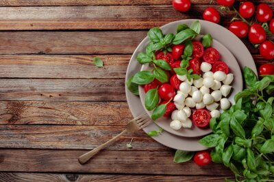 Caprese salad with tomato, mini mozzarella and basil on a old wooden table.