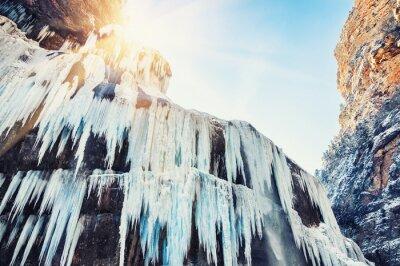 Papiers peints Cascade gelée dans les montagnes au coucher du soleil.