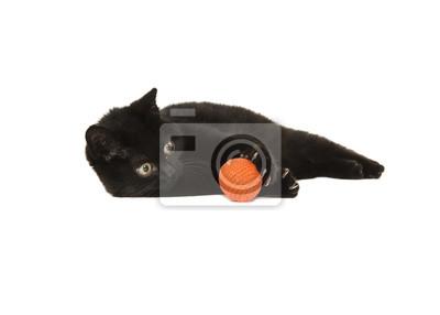 Chat chaton noir couché en jouant avec une boule orange