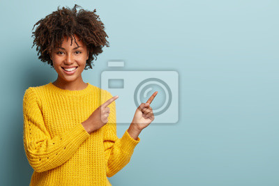 Papiers peints Cheerful Afro woman points away on copy space, discusses amazing promo, gives way or direction, wears yellow warm sweater, has pleasant smile, feels optimistic, isolated over blue background
