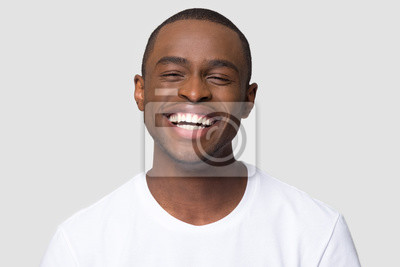 Papiers peints Cheerful happy african millennial man laughing looking at camera isolated on studio blank background, funny young black guy with healthy teeth beaming orthodontic white wide smile head shot portrait