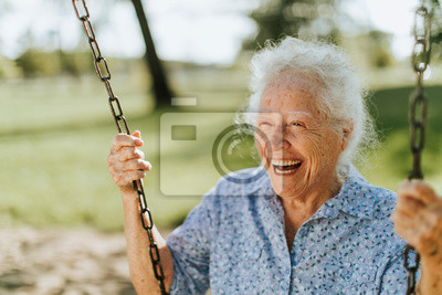Papiers peints Cheerful senior woman on a swing at a playground