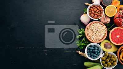 Papiers peints Choix d'aliments sains et propres: Légumes, fruits, noix, baies et champignons, persil, épices. Sur un fond noir Espace libre pour le texte.