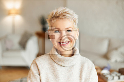 Papiers peints Close up image of happy good looking elegant fifty year old woman wearing warm cozy jumper, pearl earrings and short stylish hairdo being in good mood sitting in living room, smiling broadly at camera