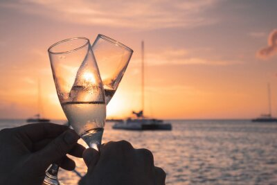Papiers peints Close-up Of Hand Holding Champagne Glass Against Sunset Sky