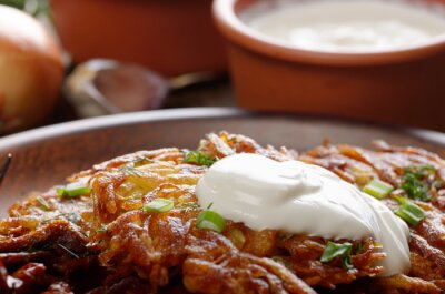 Closeup photo of fresh homemade potato pancakes in clay dish with greens and sour cream
