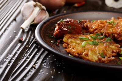 Closeup view at Homemade tasty potato pancakes in clay dish with sun-dried tomatoes
