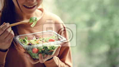 Papiers peints Closeup woman eating healthy food salad, focus on salad and fork.