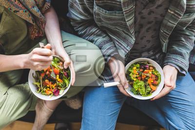 Papiers peints Couple à manger à la salade à la maison sur le canapé