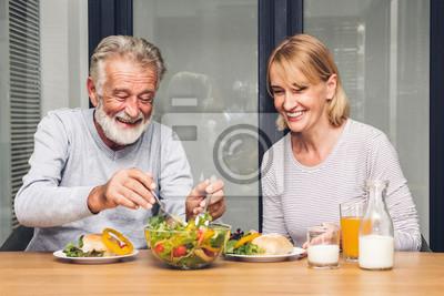 Papiers peints Couple de personnes âgées profiter de manger un petit déjeuner sain ensemble dans la cuisine. Concept de couple de retraite