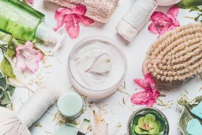 Papiers peints Crème pour la peau avec pétales de fleurs et autres produits cosmétiques et accessoires de soin du corps sur fond blanc, vue de dessus
