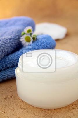 crème pour le visage et le corps dans la banque et serviette