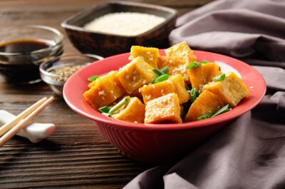 Crispy stir fried tofu cubes with chives in clay dish on wooden kitchen table with napkin and soy sauce aside