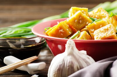 Crispy stir fried tofu cubes with chives in clay dish on wooden kitchen table with napkin chives pepper garlic and soy sauce aside