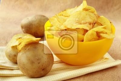 croustilles dans une tasse jaune et pommes de terre fraîches