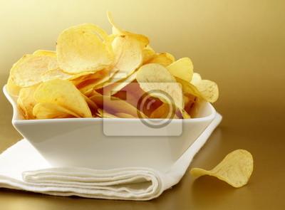 des chips dans un bol blanc sur un fond d'or