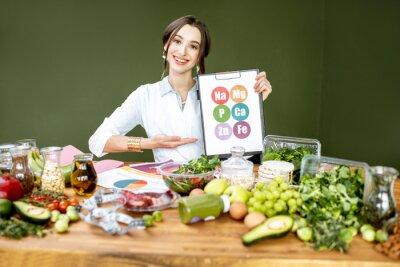 Papiers peints Diététiste montrant un régime avec des vitamines assis à la table remplie de divers produits sains à l'intérieur. Concept d'alimentation saine