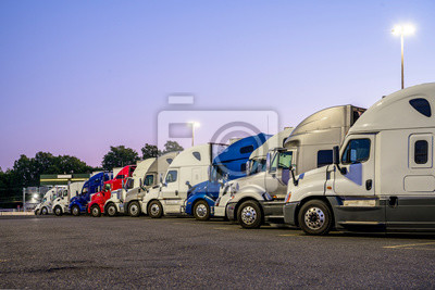 Papiers peints Different big rigs semi trucks standing in row on the night truck stop parking lot with turned on lanterns on poles waiting for morning to continue the delivery route