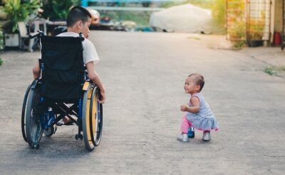 Disabled child sitting wheelchair take care  his little sister in a way that disabled kids can do with loving care,Life in the education age of children, Happy disabled kid concept.