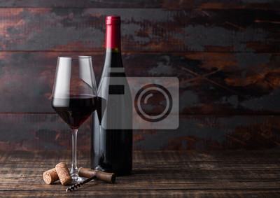 Papiers peints Elegant glass and bottle of red wine with corks and corkscrew on dark wooden background. Natural Light