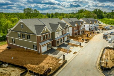 Papiers peints Elevated view of almost finished luxury townhouses with two single car garages, brick and shake and shingle siding, gable roof with attic vent on a new residential development in Maryland USA