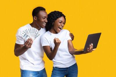 Papiers peints Emotional black couple celebrating win with laptop and cash