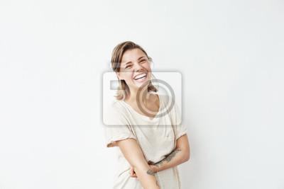 Papiers peints Enthousiaste heureux jeune fille belle regarde la caméra en souriant en riant sur fond blanc.