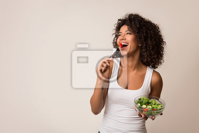 Papiers peints Excited lady eating healthy salad over light background