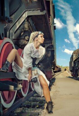 Papiers peints Femme dans la robe vintage est assis sur la roue de la locomotive.