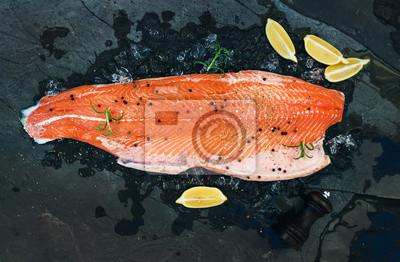 Filet de saumon cru avec du citron et du romarin sur la glace écaillée sur fond de pierre sombre