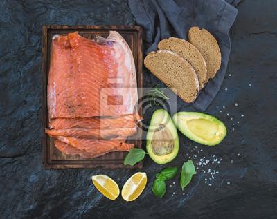 Filet de saumon fumé au citron, avocat, herbes fraîches et élevés sur une planche de service en bois sur fond de pierre sombre
