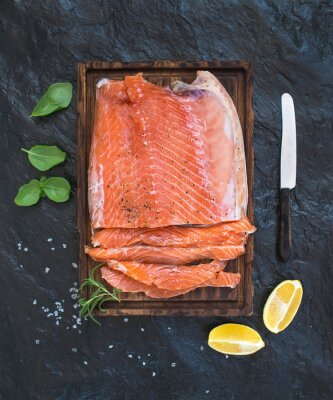 Papiers peints Filet de saumon fumé au citron, herbes fraîches et élevés sur une planche de service en bois sur fond de pierre sombre