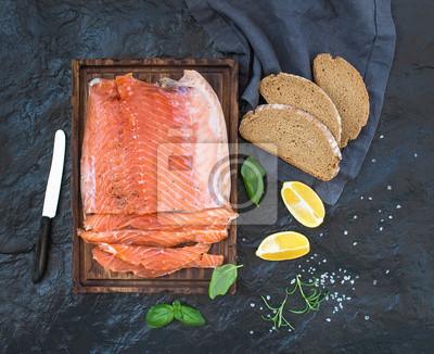 Filet de saumon fumé au citron, herbes fraîches et élevés sur une planche de service en bois sur fond de pierre sombre