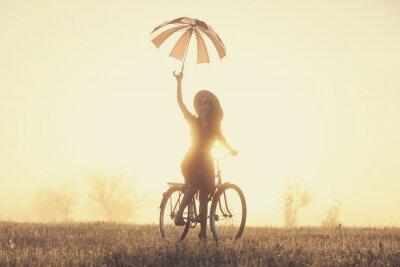 Papiers peints Fille avec le parapluie sur un vélo dans la campagne dans le temps le lever du soleil