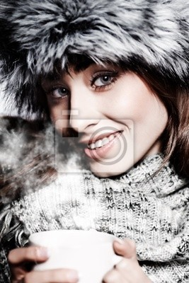 Fille soufflant sur boisson chaude habillé en vêtements d'hiver