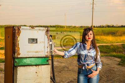 Fille sur une vieille station de gaz