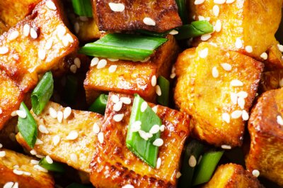 Flat lay background of Close Up view at crispy fried tofu pieces with chives and sesame