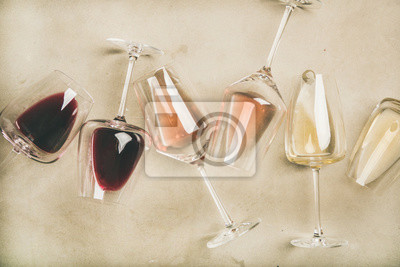 Papiers peints Flat-lay of red, rose and white wine in glasses over grey concrete background, top view. Wine bar, winery, wine degustation concept