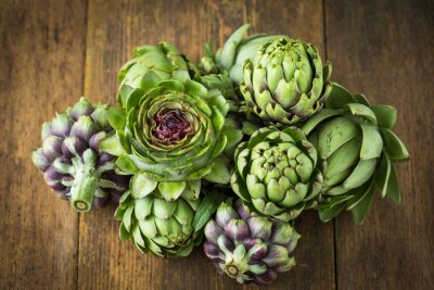 Fresh and raw artichoke on the wooden table