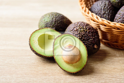 Fresh hass avocado fruit in basket on wooden background