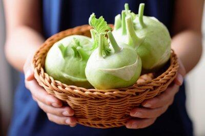 Fresh kohlrabi in basket holding by hand, organic vegetables