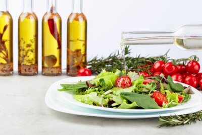 Fresh mixed salad with cherry tomatoes on white plate.