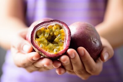 Fresh passion fruit holding by woman hand, healthy eating