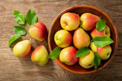 fresh pears with leaves in a bowl on a wooden table, top view