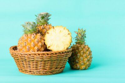 Fresh pineapple fruit in a basket on pastel green background, Tropical fruit