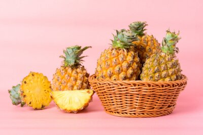 Fresh pineapple fruit in a basket on pastel pink background, Tropical fruit