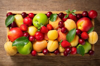 fresh ripe fruits and berries in a wooden box