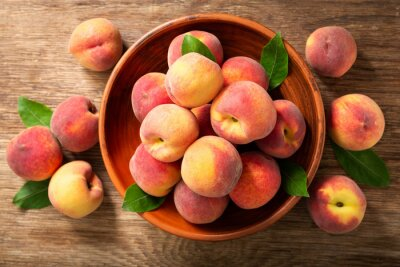 fresh ripe peaches with leaves in a bowl, top view